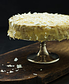 A lemon cake topped with white chocolate on a cake stand