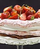 A layered meringue cake with raspberry cream, truffle cream and strawberries
