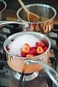 Jam making: A pot of fruit and preserving sugar on a hob