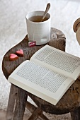 Old, rustic wooden stool used as side table for cosy afternoon break with tea and chocolates