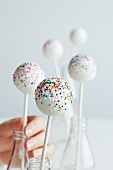 Hand Placing White Cake Pops with Colorful Sprinkles into Bottles