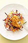 A raw salad with breaded chicken