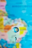 An artistic shot of a globe seen though a drop of water