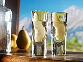 Two glasses of William's pear schnapps against an alpine backdrop