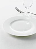 Weisser Teller, Weinglas und Gabel