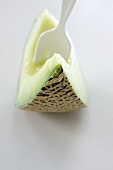A fork stuck in a slice of honeydew melon