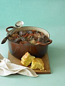 Pot of Hearty Beef Stew; Corn Bread on a Cutting Board