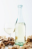 A bottle and a glass of wine with corks