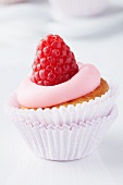 A mini muffin in a muffin case topped with raspberry mousse and a raspberry