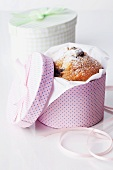 A chocolate-chip muffin in a round gift box