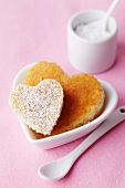 A heart-shaped sponge cake with icing sugar