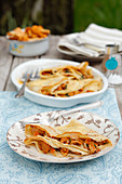 Crepes with chanterelle mushrooms on a table in a garden