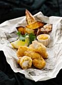 Fish & Chips mit Pommes auf Zeitungspapier