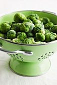 Fresh Brussels Sprouts in a Green Colander