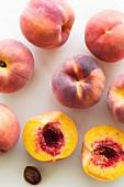 Pfirsiche, ganz und halbiert