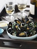 Bowl of Steamed Mussels with Glasses and Bottle of White Wine on a Tray