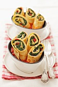 Pancake rolls filled with spinach and ham in tomato sauce