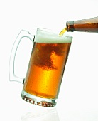Beer pouring From a Bottle into a Glass Mug; White Background