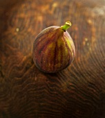 One Fig on Wooden Background