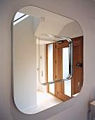 Wandspiegel mit gerundeten Formen reflektiert den Hauseingang