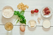 Ingredients for pasta carbonara with tomatoes and prosciutto