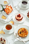 Assorted French pastries, tea and coffee on a table set in white