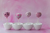 Four purple cake pops in bowls of sugar