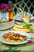 Grilled chicken kebabs on orange salsa