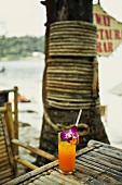 A glass of freshly squeezed orange juice with orchids on a beach (Thailand)