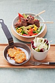 Beef kebabs on avocado-corn salad, fennel salad and potato pancakes