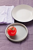 One tomato on a plate and an empty plate