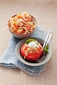 Shrimp kebabs on spaghetti and stuffed tomatoes with spaghetti