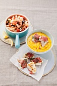 Shrimp with vegetables, sheep's cheese and couscous and pollock with ham and sage on saffron risotto