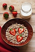 Bowl of Rolled Oat Cereal with Strawberries; Jar of Milk