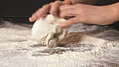 Dough being kneaded on a floured work surface