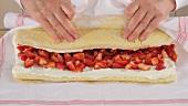 Biskuitplatte mit Erdbeer-Sahne-Füllung aufrollen