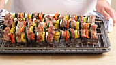 Taking grilled meat and vegetable skewers out of the oven