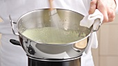 Beating crème in bowl over pan of simmering water