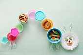 A caterpillar of colourful crockery with snacks
