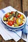 Tomato salad with yellow and red tomatoes, chickpeas and pesto dressing