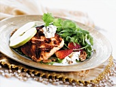 Fried salmon fillet with salad, strawberries, walnuts and sliced apples
