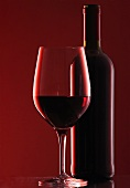 Glass of red wine and bottle of red wine against a red background