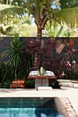 Set table beneath palm trees in garden next to pool
