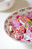 Red and white marbled sweets and sweet packaging on a nostalgic floral-patterned plate