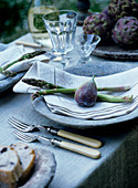 Place setting with fig and green asparagus on linen napkin and rustic stone plate