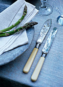 Antique knives with ivory handles next to asparagus arranged on stone plate