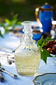 A glass carafe of white wine on a garden table