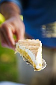 A person holding a slice of lemon cake with meringue