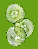 Three slices of cucumber on a green surface