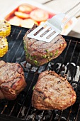 Fillet steaks stuffed with pesto on barbecue